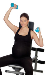Pregnant woman lifting weights in the gym
