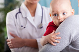 Baby boy in the arms of mother at doctor's office