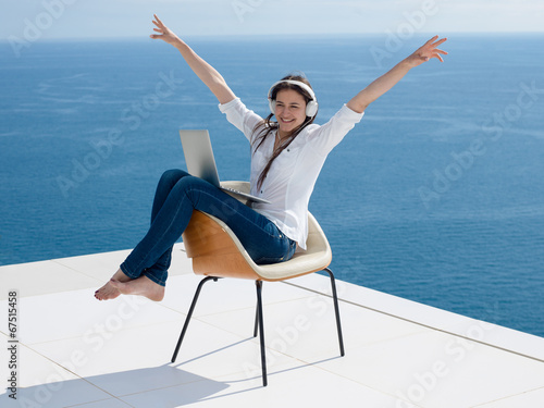 canvas print picture relaxed young woman at home working on laptop