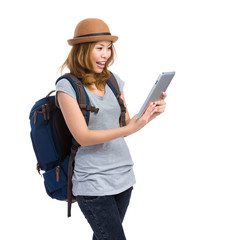 Woman with backpack look at digital tablet