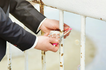 Lock with keys in hands of  groom and bride