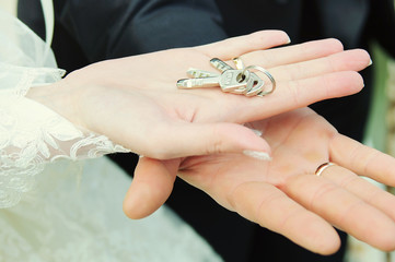 Key in hands of  groom and bride