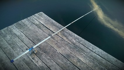 The rod is laying on old wooden pier