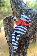 Handmade toy cat relaxing on a tree