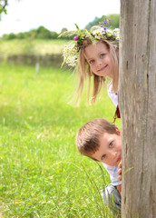 Brother and sister peeking of rural fence
