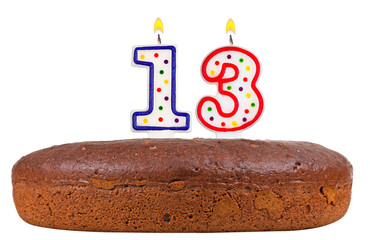 birthday cake with candles number thirteen isolated on white