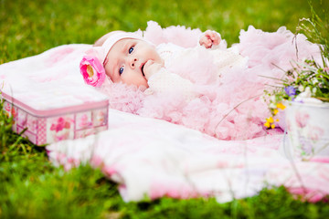cute newborn girl in pink skirt gnaws fingers