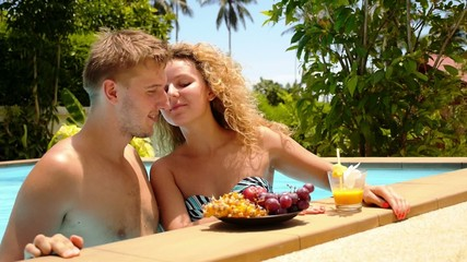 Happy Smiling Couple Eating Fruits Together in Swimming Pool.