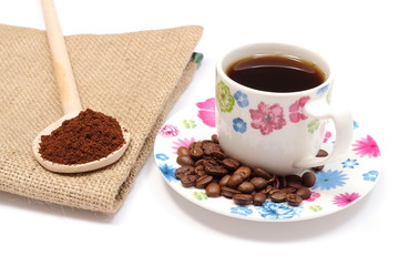 Ground coffee on wooden scoop and cup of hot beverage