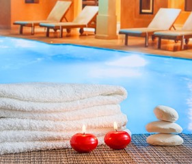 Spa massage with towel stacked red candles near swimming pool