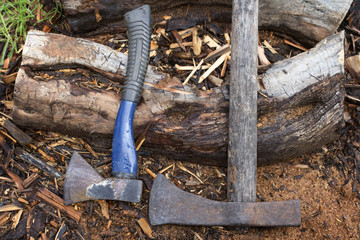 New and old axe on the ground near the wooden stump