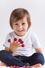 Adorable boy, having fun with raspberries