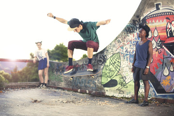 Skater in movement making a trick with his skate with friends
