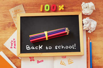 top view of blackboard with the phrase back to school, stack of