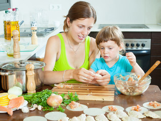woman with baby cooking fish dumplings (pelmeni) together