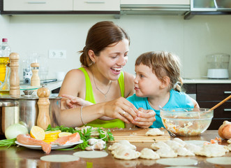 woman with a smiling girl dumplings fish cooking together at ho