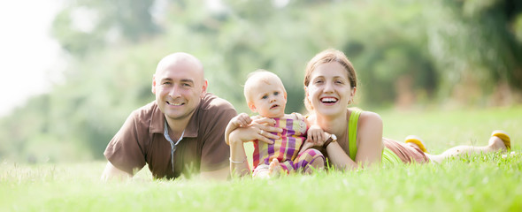 Happy family of three in grass