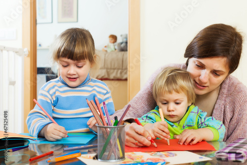Woman and two children  with pencils in home