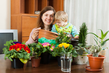 Mother with a toddler transplanting potted flowers