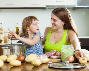 Happy mother with child cooking soup f