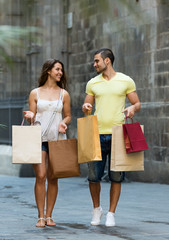 smiling loving couple with shopping bags at city