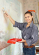 woman paints wall