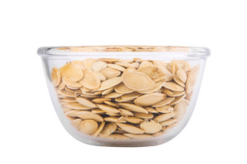 Pumpkin seeds in a transparent bowl isolated on white background