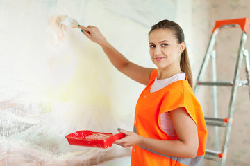 house painter paints wall with brush