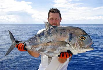 Pêcheur tenant une carangue prise à la ligne