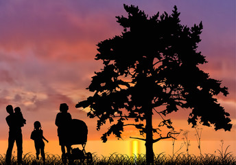 family and pine silhouettes at sunset