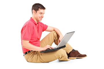 Young man working on laptop seated on the floor