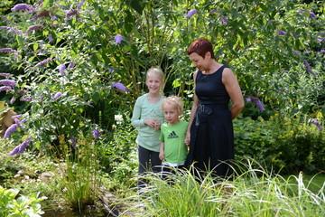 Mutter mit Kindern im Garten