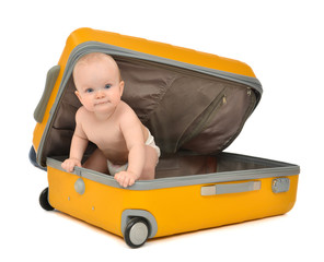 Happy infant baby toddler sitting in yellow plastic travel suitc
