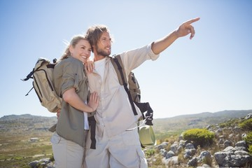 Hiking couple standing on mountain terrain looking around