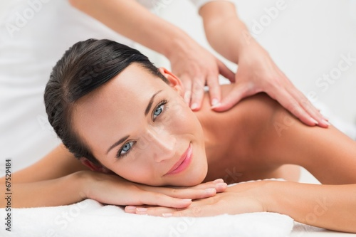 canvas print picture Beautiful brunette enjoying a shoulder massage smiling at camera