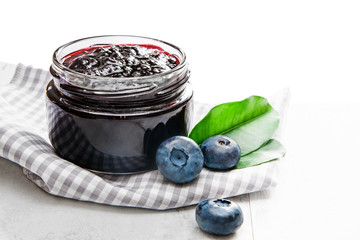 Jar with blueberry jam and scattered berries on wooden table