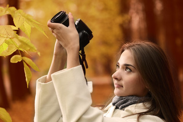 girl with camera in autumn forest