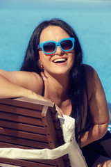 Portrait of smiling young woman laying on sunbed