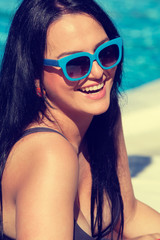 Smiling young woman laying on sunbed