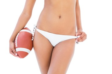 Fit girl in white bikini holding american football