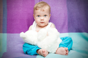 Cute child with toy bear against bright background