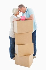 Older couple smiling at each other with moving boxes and piggy b