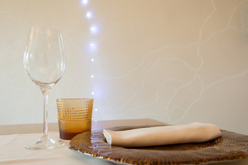 Setting table with dish, glasses and napkin