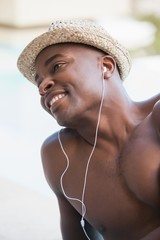 Shirtless man smiling and listening to music
