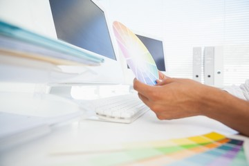 Designer working at desk holding colour wheel