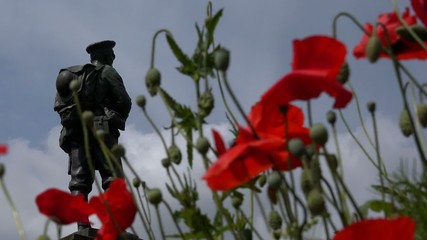 Soldiers World War Memorial Statue with red poppies
