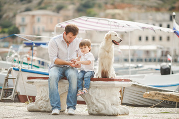 Father and son sits with dogs on a bench near the sea