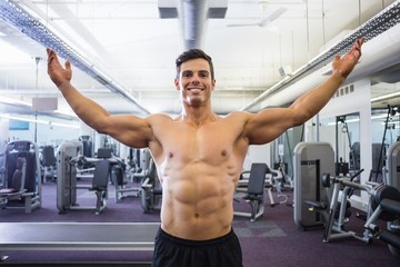 Shirtless bodybuilder with arms raised in gym