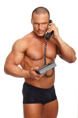 Muscular man speaks into telephone on isolated background