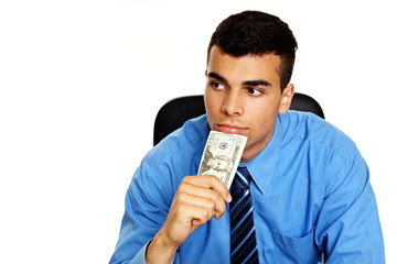 Thoughtful young man in blue shirt with money